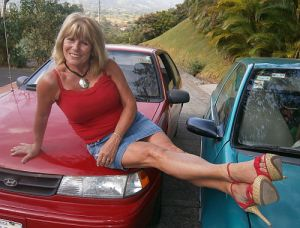 Carole Jean on Newly painted red car next to Victor's turquoise car